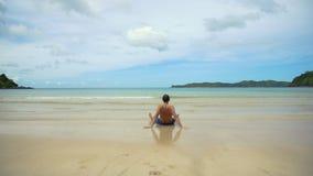 Hombre que se sienta en la playa fotos de archivo