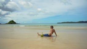 Hombre que se sienta en la playa metrajes