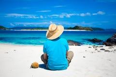 Hombre que se sienta en la playa tropical de la isla Fotos de archivo libres de regalías