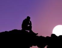 Hombre que se sienta en la puesta del sol Imagenes de archivo