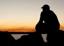 Hombre que se sienta en la puesta del sol Fotos de archivo libres de regalías