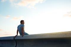 Hombre que se sienta en la puesta del sol Foto de archivo libre de regalías