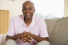 Hombre que se sienta en la sonrisa de la sala de estar foto de archivo libre de regalías
