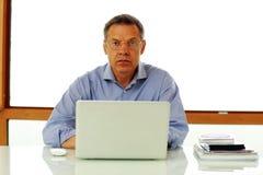 Hombre que se sienta en la tabla con el ordenador portátil Imagenes de archivo