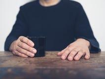Hombre que se sienta en la tabla con la taza imagenes de archivo