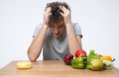 Hombre que se sienta en la tabla con las verduras Imagen de archivo