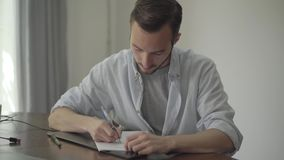 Hombre que se sienta en la tabla que escribe algo en el papel en casa Concepto de la profesión, escritor, redactor de anuncios, r almacen de video