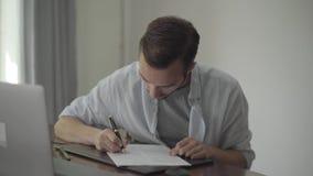 Hombre que se sienta en la tabla que escribe algo en el papel en casa Concepto de la profesión, escritor, redactor de anuncios, r metrajes