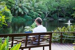 Hombre que se sienta en la ubicación y el trabajo tropicales Fotos de archivo libres de regalías