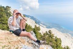 Hombre que se sienta en las montañas que miran a través de los prismáticos Imagen de archivo libre de regalías