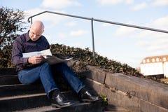 Hombre que se sienta en los pasos que leen un periódico Fotografía de archivo libre de regalías