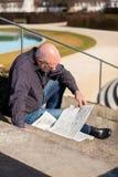 Hombre que se sienta en los pasos que leen un periódico Imagen de archivo