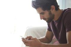 Hombre que se sienta en mensaje de texto de Sofa Using Mobile Phone To Fotografía de archivo libre de regalías