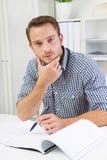 Hombre que se sienta en oficina Imagen de archivo libre de regalías