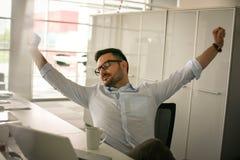 Hombre que se sienta en oficina y estirado Havin del hombre de negocios imagenes de archivo