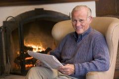 Hombre que se sienta en sala de estar por la chimenea Imagenes de archivo
