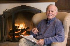 Hombre que se sienta en sala de estar por la chimenea foto de archivo