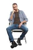 Hombre que se sienta en silla imagenes de archivo