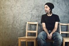 Hombre que se sienta en silla de madera y esperar Foto de archivo