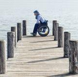 Hombre que se sienta en silla de ruedas fotografía de archivo libre de regalías