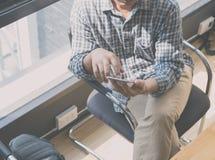 hombre que se sienta en silla usando el teléfono elegante Imagen de archivo
