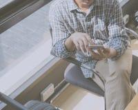 hombre que se sienta en silla usando el teléfono elegante Foto de archivo libre de regalías