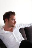 Hombre que se sienta en sofá Fotos de archivo