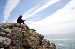 Hombre que se sienta en tapa del acantilado Foto de archivo libre de regalías