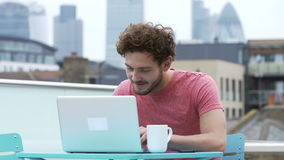 Hombre que se sienta en terraza del tejado usando el ordenador portátil y el teléfono móvil metrajes