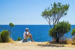 Hombre que se sienta en un acantilado por el mar Fotos de archivo