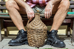 Hombre que se sienta en un banco con la bombona Imagen de archivo libre de regalías