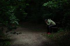 Hombre que se sienta en un banco en punto ligero en la trayectoria de bosque, rodeada con la oscuridad, cubriendo su cara con sus fotografía de archivo libre de regalías
