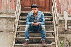 Hombre que se sienta en una escalera de madera Casa vieja Foto de archivo