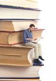 Hombre que se sienta en una pila de libros Fotografía de archivo libre de regalías