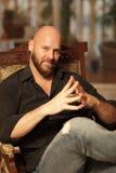 Hombre que se sienta en una silla de madera Foto de archivo libre de regalías