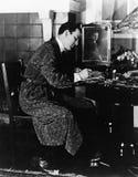 Hombre que se sienta en una silla y escritura (todas las personas representadas no son vivas más largo y ningún estado existe Gar Foto de archivo libre de regalías