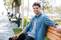 Hombre que se sienta en una sonrisa del banco Imagen de archivo libre de regalías