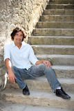 Hombre que se sienta encendido abajo Imagen de archivo