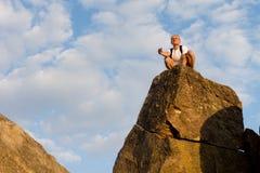 Hombre que se sienta encima de una alta roca Imágenes de archivo libres de regalías