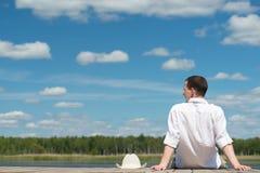 Hombre que se sienta por el lago Imágenes de archivo libres de regalías