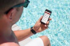 Hombre que se sienta por la piscina y que comprueba el correo electrónico su smartphone Imágenes de archivo libres de regalías