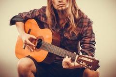 Hombre que se sienta que toca la guitarra Fotografía de archivo