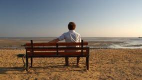 Hombre que se sienta solamente en la playa almacen de metraje de vídeo