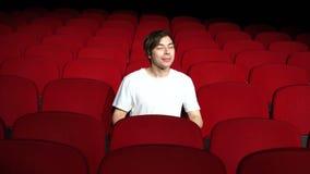 Hombre que se sienta solamente en pasillo vacío del cine o película del teatro y de la observación funcionamiento o metrajes