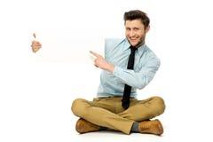 Hombre que se sienta y que señala en el cartel en blanco Imagen de archivo