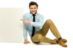 Hombre que se sienta y que señala en el cartel en blanco Imágenes de archivo libres de regalías