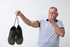 Hombre que se siente mal el olor de los zapatos foto de archivo libre de regalías