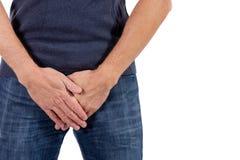 Hombre que se sostiene la uretra en dolor Problemas de los hombres en el fondo blanco Concepto MÉDICO foto de archivo libre de regalías