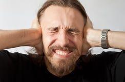 Hombre que se sostiene los oídos Fotografía de archivo libre de regalías