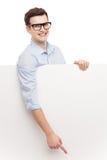 Hombre que señala en el cartel en blanco Imagen de archivo
